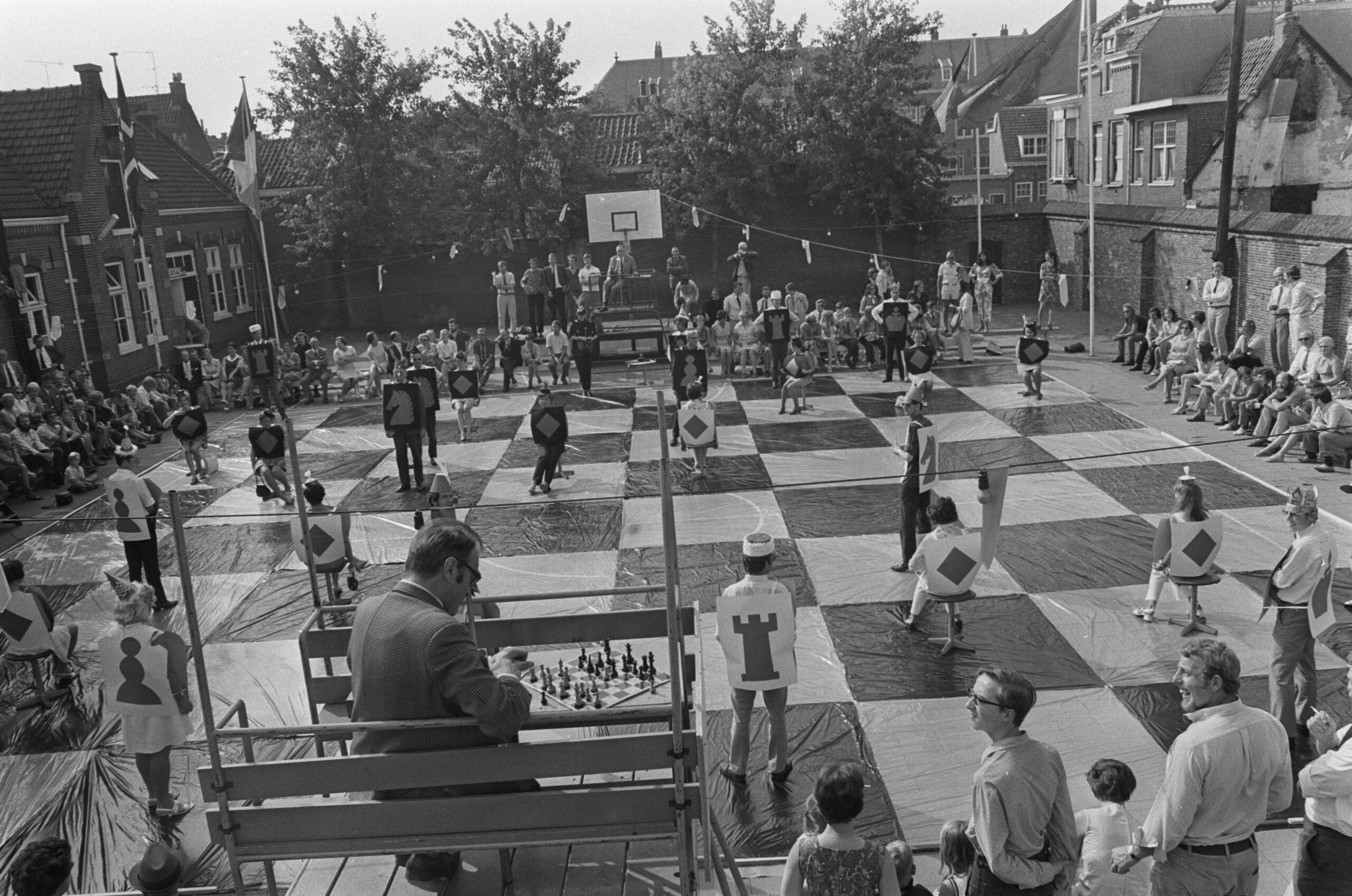Godfried Bomans en Dr. Max Euwe spelen schaak met levende stukken